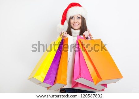 brunette woman in santa hat holding shopping bags