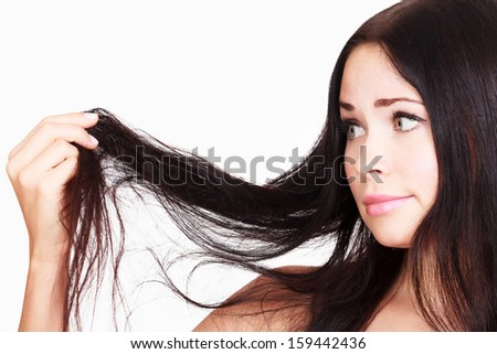 brunette woman is not happy with her fragile hair, white background, copyspace - stock photo