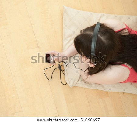 Brunette woman listening music lying down on the floor at home - stock photo