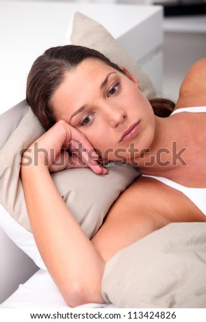 Brunette woman lying in bed - stock photo