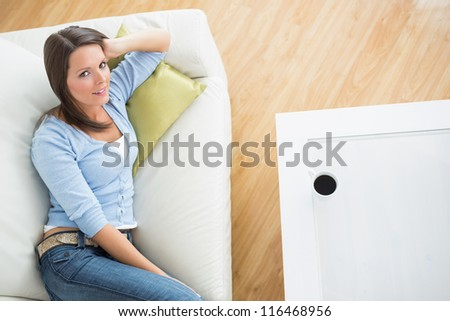 Brunette woman lying on sofa in the living room