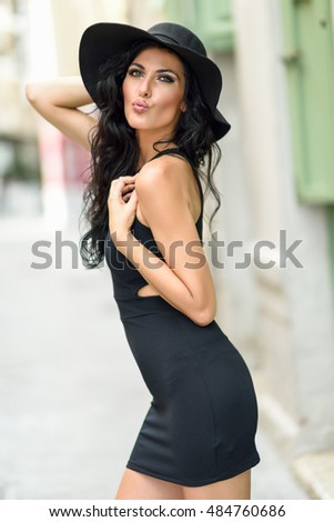 Brunette woman, model of fashion, wearing black seductive dress and sun hat in the street. Young girl with curly hairstyle blowing a kiss in urban background