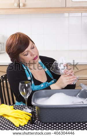 Brunette woman polishing glasses in domestic kitchen
