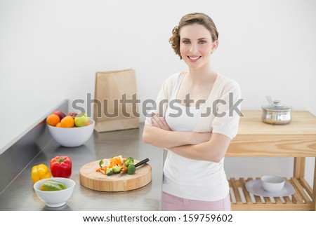 Brunette woman posing in kitchen with arms crossed in her kitchen at home