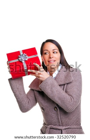 Brunette woman shaking her present to see whats inside, isolated on a white background. - stock photo