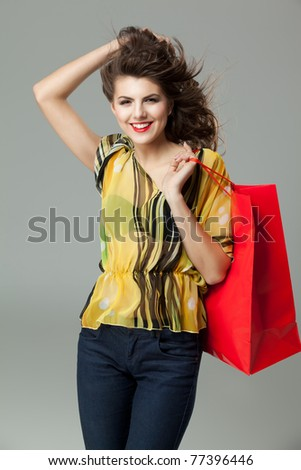 brunette woman shopping red bag wind hair - stock photo