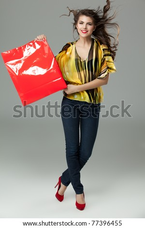 brunette woman shopping red bag wind hair