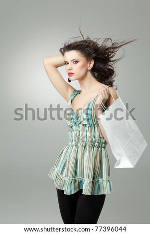 brunette woman shopping white bag wind hair - stock photo
