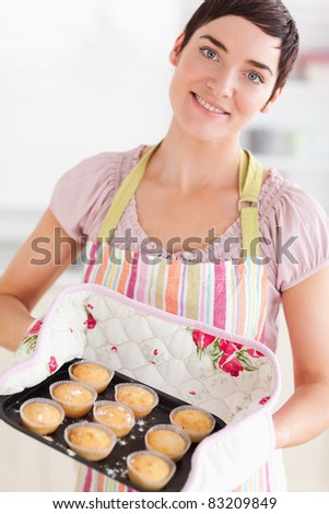 Brunette woman showing muffins in a kitchen - stock photo