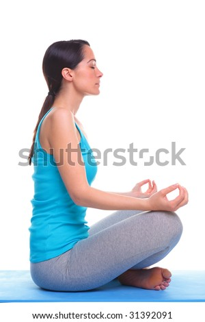 Brunette woman side view sat on a yoga mat in the lotus position, isolated on a white background. - stock photo