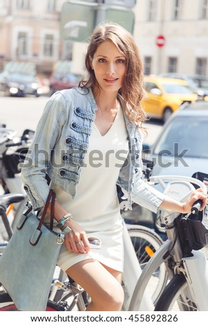 Brunette woman sitting on bicycle near bike parking
