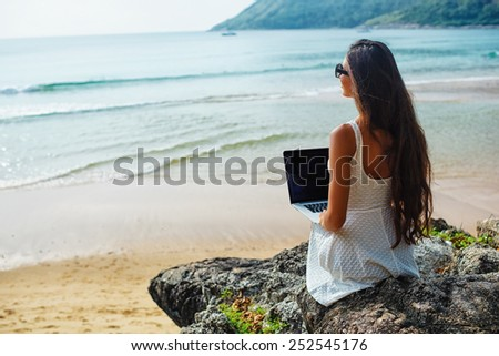 brunette woman sitting on the rock with laptop near  sea - stock photo