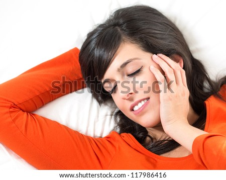 Brunette woman sleeping peacefully in white bed with her hand in her face. Serene and happy expression. - stock photo