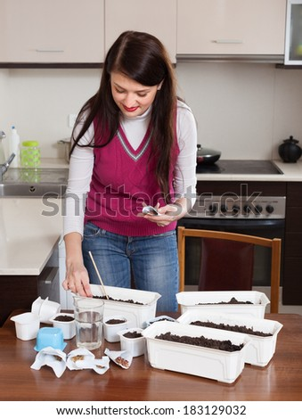 Brunette woman sowing sprouts at her  home