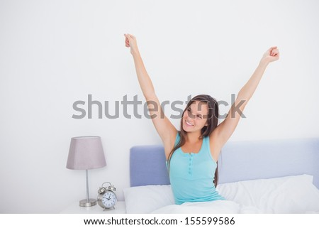Brunette woman stretching her arms in bed in the morning in bedroom at home - stock photo