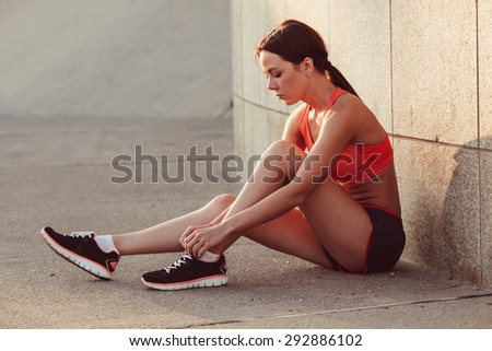 brunette woman trying running shoes getting ready for jogging - stock photo