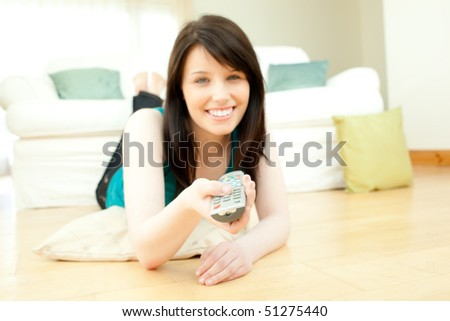 Brunette woman watching television in the living room - stock photo