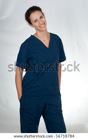 brunette woman wearing blue scrubs against white background - stock photo