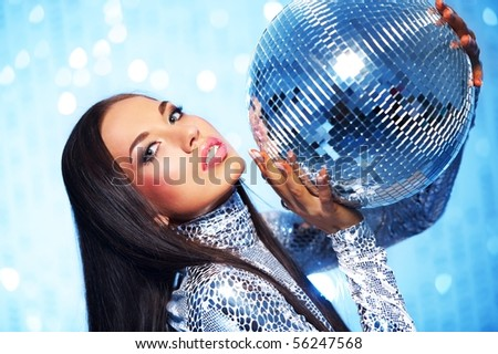 Brunette woman with a disco ball over abstract background - stock photo