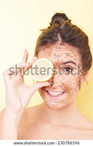 brunette woman with a scrub applied to her face and a slice of lemon covering face - stock photo