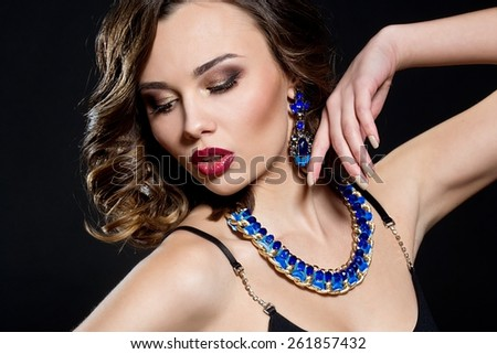 Brunette woman with curly hair and blue jewelry