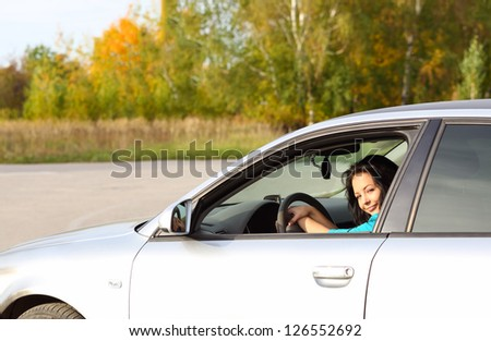 Brunette young girl driving a car - stock photo
