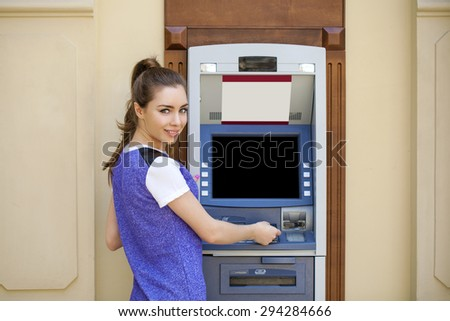 Brunette young lady using an automated teller machine. Woman withdrawing money or checking account balance - stock photo