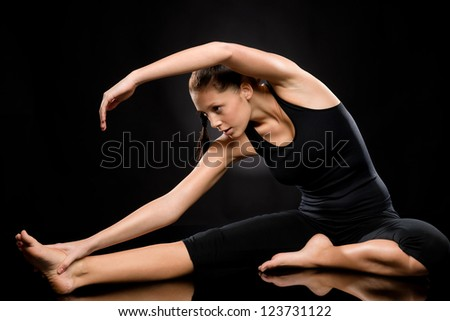 Brunette young woman exercising yoga in separate leg stretching pose - stock photo