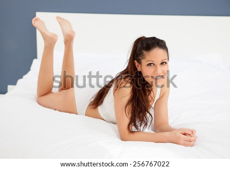 Brunette young woman resting in her bed - stock photo