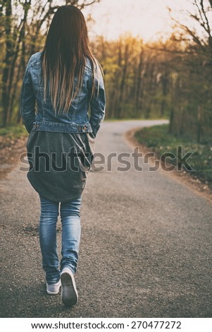 Brunette young woman walking the forest road - stock photo