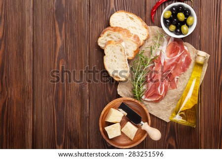 Bruschetta ingredients - prosciutto, olives, cheese. Top view on wooden table - stock photo