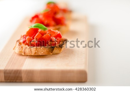 Bruschetta is an italian food made of chopped tomatoes, garlic, basil and fresh herbs on a toasted bread. These are traditionally served as snacks or antipasti (appetizers). - stock photo