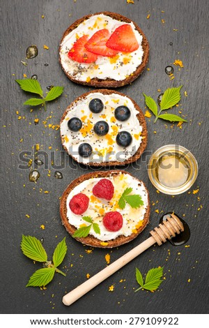 Bruschetta or toast with goat cheese, berries and honey. top view - stock photo