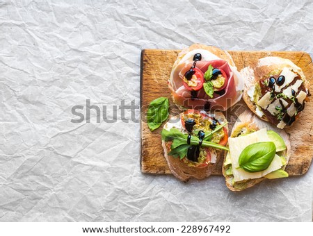 Bruschetta set on a rustic wooden board over a white paper background with a copy space  - stock photo