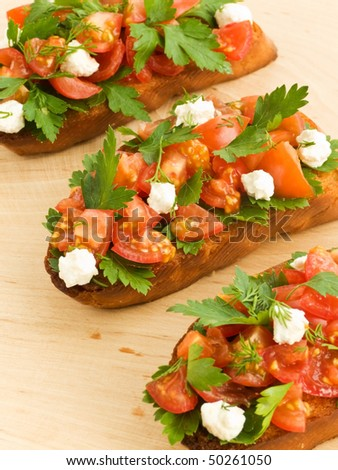 Bruschetta with cherry tomatoes, cottage cheese and parsley. Shallow dof. - stock photo