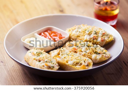 Bruschetta with chicken, tomato, parmesan and cheddar cheese with romantic candle light dinner on wooden table background, for appetizer - stock photo