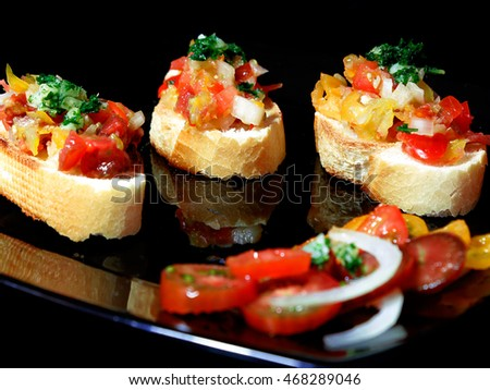 Bruschetta with different varieties of tomatoes, parsley and garlic