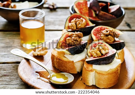 bruschetta with figs, honey, goat cheese and walnuts on a dark wood background. tinting. selective focus on walnut - stock photo