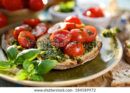 Bruschetta with fresh cherry tomatoes and aromatic herb pesto - stock photo