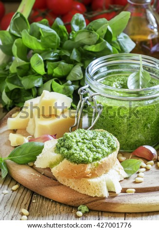 Bruschetta with fresh pesto sauce, hard cheese, nuts, basil, vintage wooden background, selective focus - stock photo