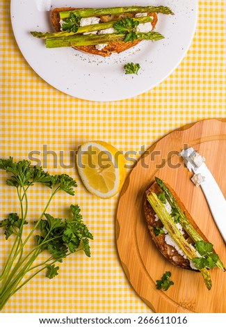 Bruschetta with goat cheese and grilled asparagus on  yellow textile background - stock photo