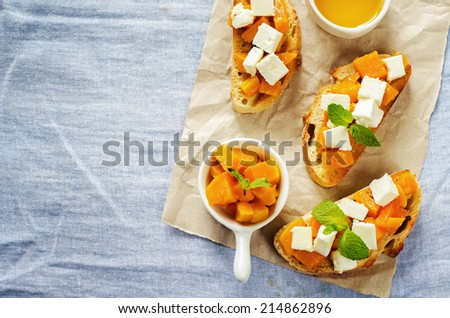 bruschetta with honey pumpkin and goat cheese on a blue background. tinting. selective focus on mint on the middle bruschetta - stock photo