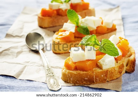 bruschetta with honey pumpkin and goat cheese on a blue background. tinting. selective focus on mint - stock photo