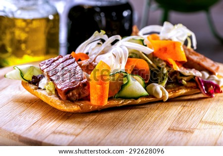Bruschetta with meat and vegetable salad close-up on wooden board  - stock photo