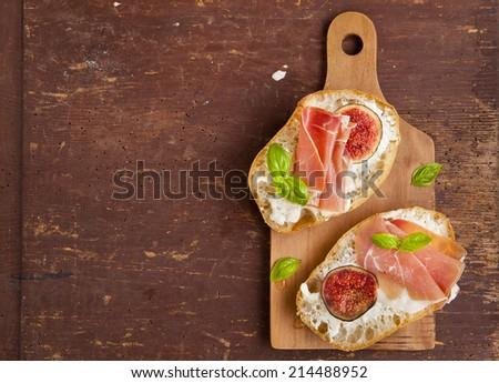 bruschetta with prosciutto ham & figs with white cheese. fresh basil. italian appetizer. - stock photo