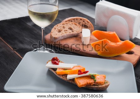 Bruschetta with pumpkin feta cheese and tomatoes. Light dinner with glass of white wine in a restaurant. - stock photo
