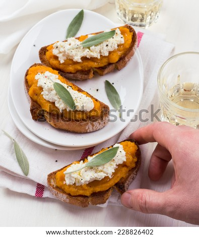 Bruschetta with pumpkin puree, ricotta and sage on a white plate - stock photo