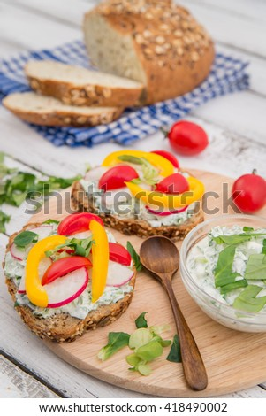 bruschetta with radish, cheese and greenery on wooden table - stock photo