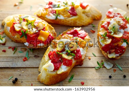Bruschetta with roasted bell pepper, goat cheese, garlic and herbs - stock photo