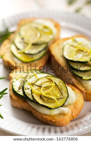 Bruschetta with stewed zucchini, mozzarella, rosemary and lemon zest - stock photo